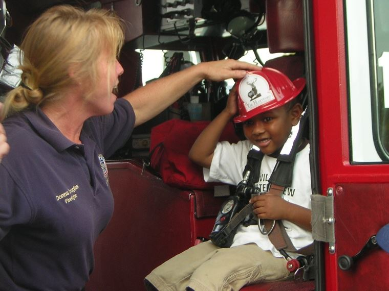 Firefighter Placing a Fire Hat on a Child